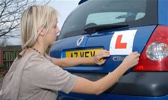 Woman putting learner plates on blue Renault Clio vehicle